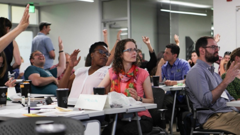 Faculty members raising their hands in class