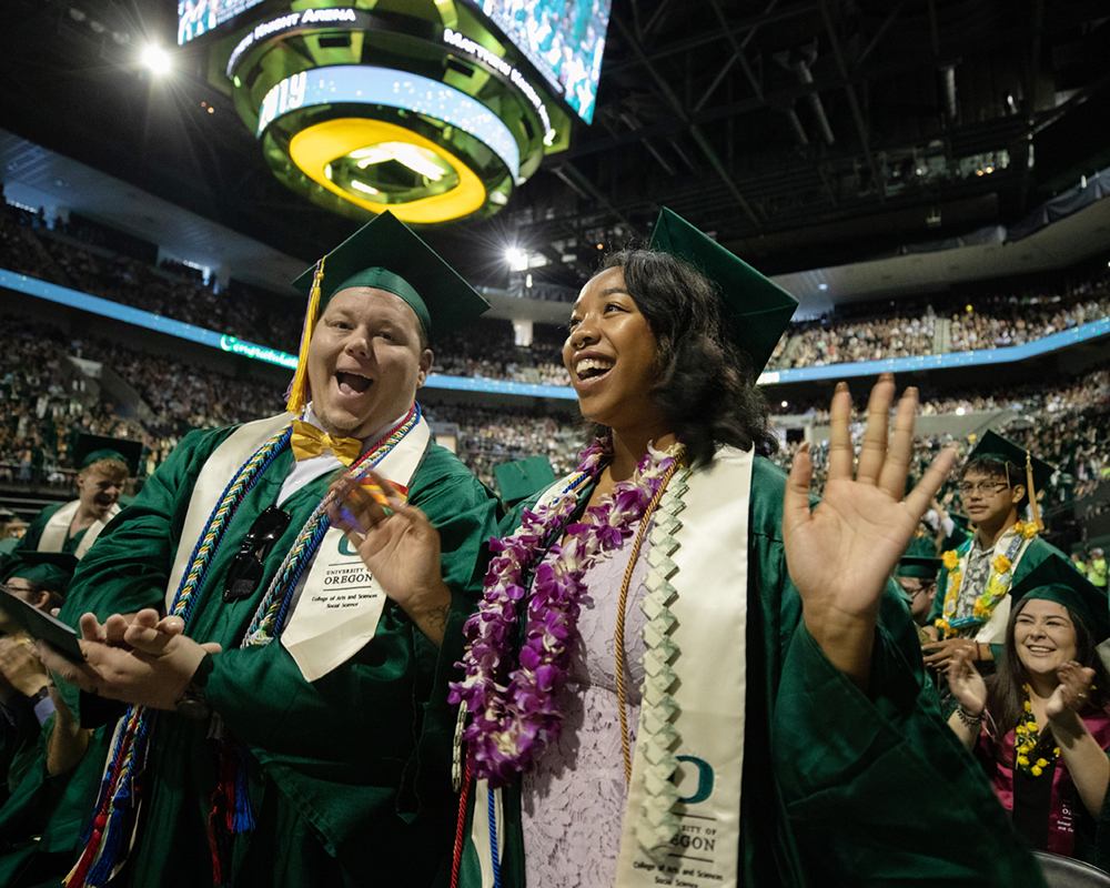 two students at the UO commencement ceremony in Matthew Knight Arena